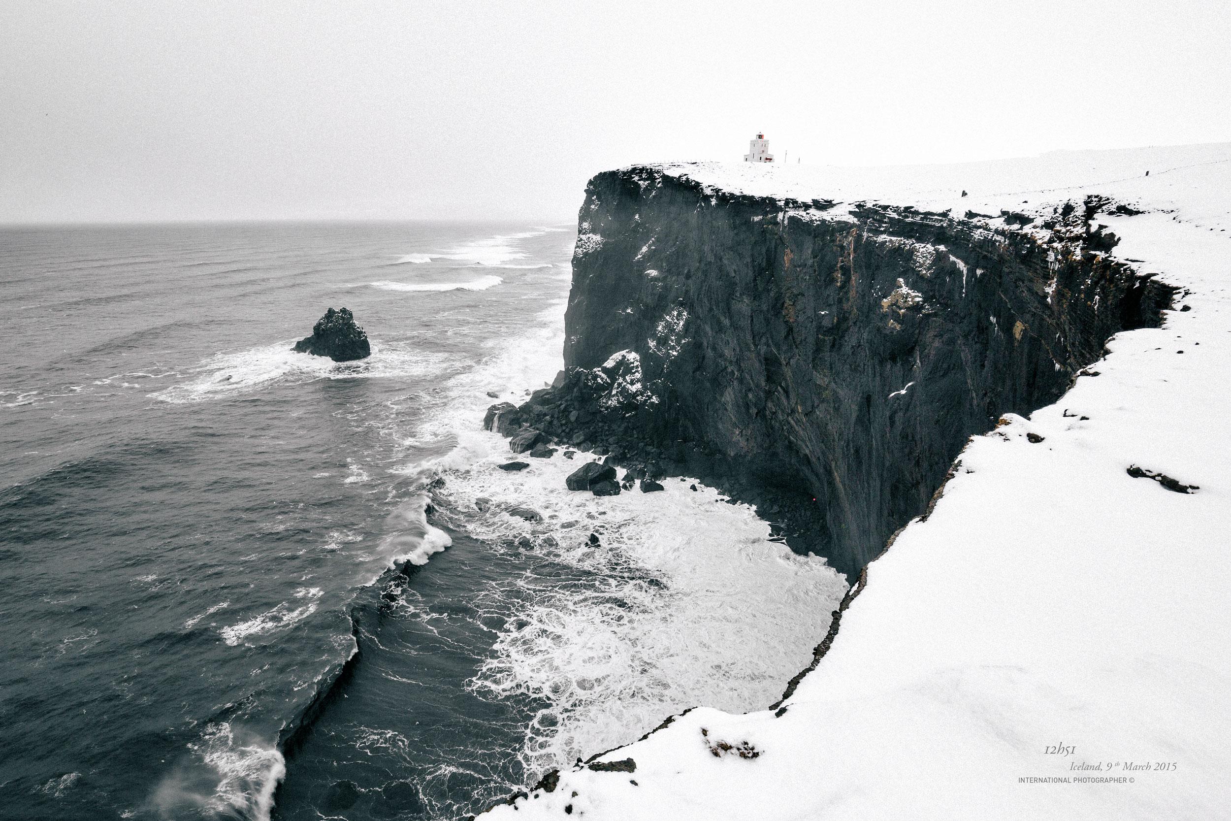 Le phare de Dyrholaey sous la neige devant la falaise